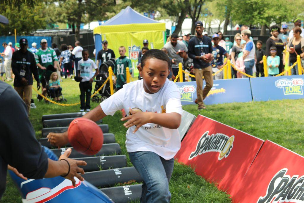 A young boy participates in one of the many activities available at the NFL Draft