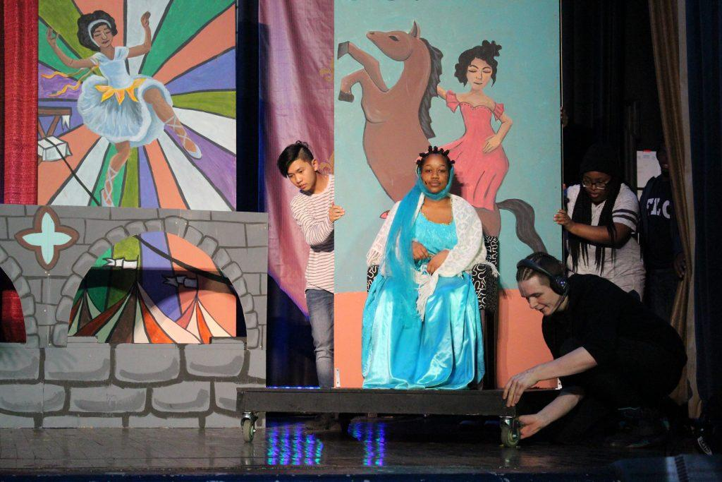 Stage Crew members Daniel Castro, Tai Dang, and Anache Shivers push a stage prop carrying Erin Davis.