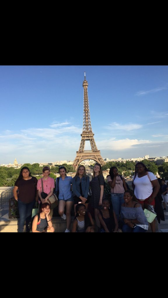 The FLC travel club poses in front of the Eiffel Tower.